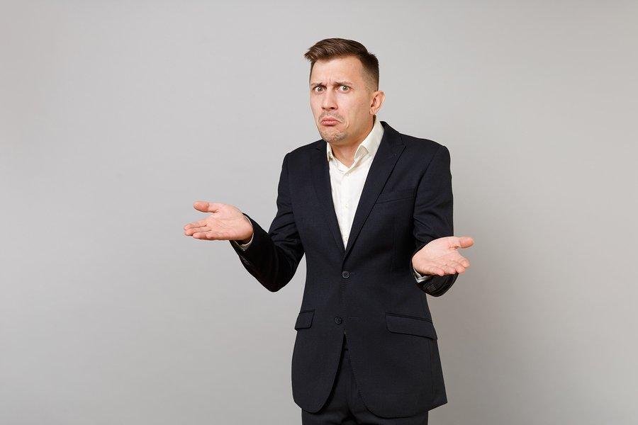 Confused businessman shrugging